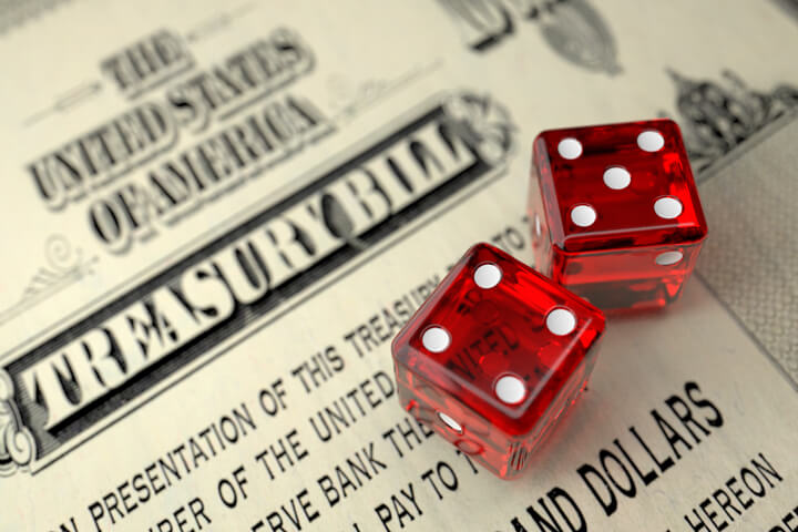 Old U.S. Treasury Bill with two dice concept for risk of investing in government treasuries