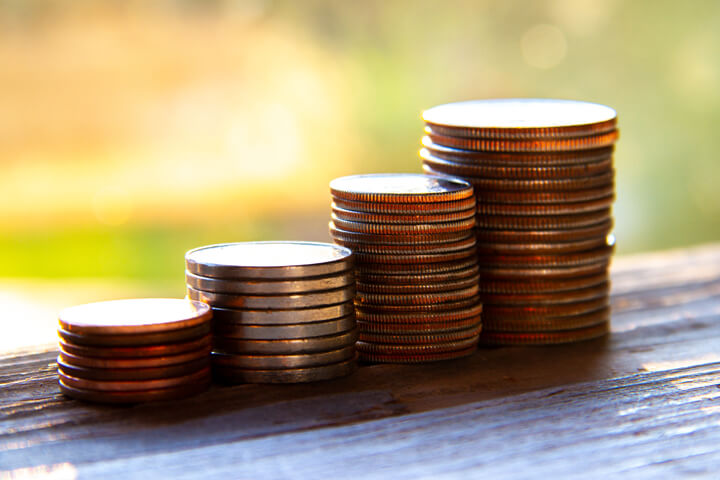 Stacks of pennies, nickels, dimes, and quarters in morning light
