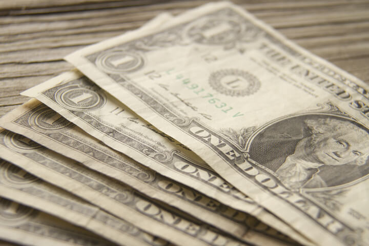 Free photo of dollar bills fanned out on wood background