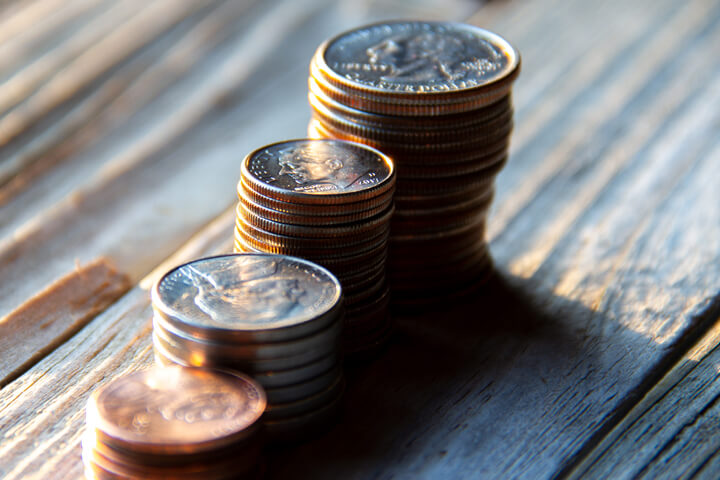 Increasing stacks of pennies, nickels, dimes, and quarters like chart in morning light