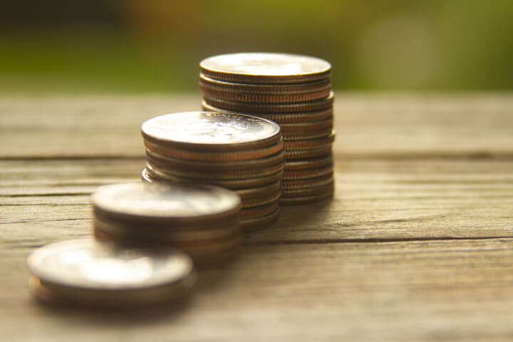 Free photo of increasing stacks of quarters with background bokeh angled view