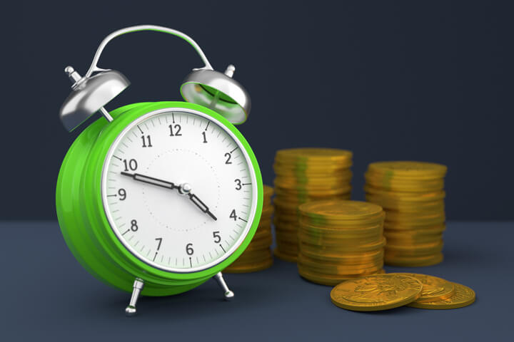Concept image with clock and stacks of gold coins for savings, time value of money, or compound interest