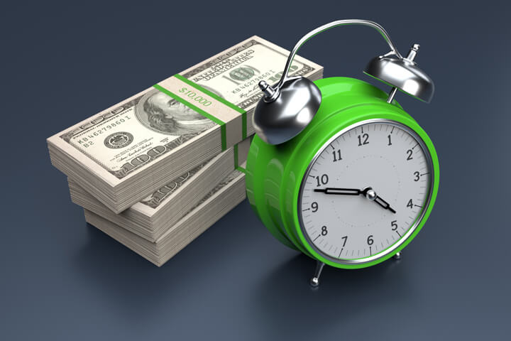 Concept image of clock and stacks of bills on dark background demonstrating cost over time or time is money