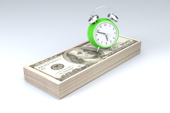 Clock sitting on stack of money concept image for time is money, time value of money, or retirement