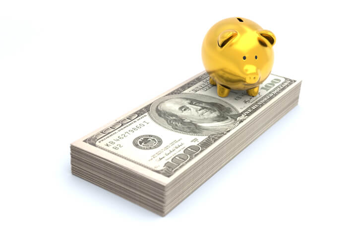 Gold piggy bank sitting on stack of Benjamins representing wealth, savings, investment, or retirement