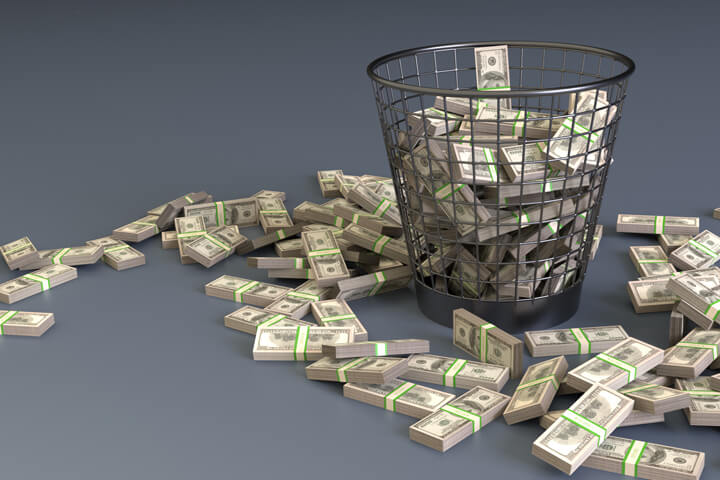 Bundles of U.S. currency in trash can concept for waste or throwing money away