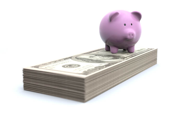 Concept photo of pink piggy bank standing on top of stack of U.S. 100 dollar bills