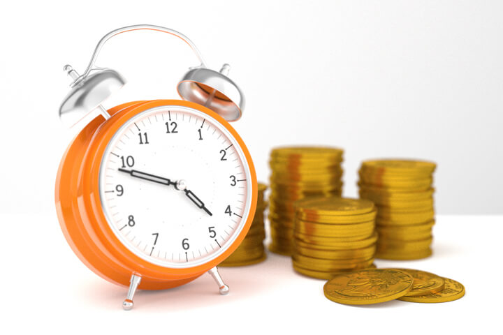 Concept of orange clock with stacks of U.S. gold coins