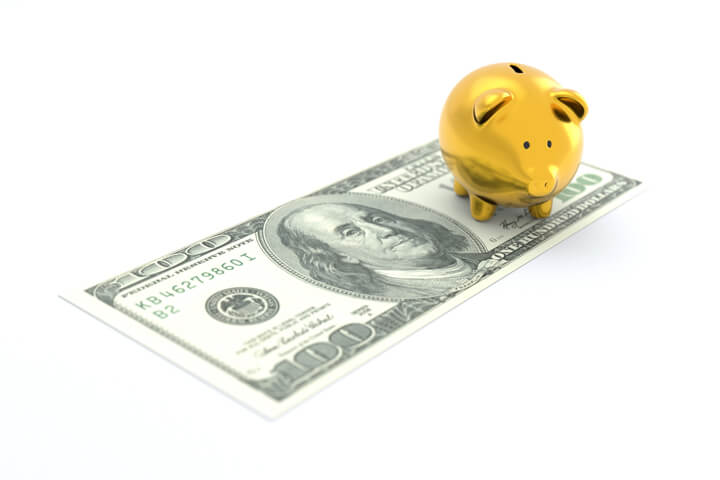 Gold piggy bank sitting on one 100 dollar U.S. bill concept image