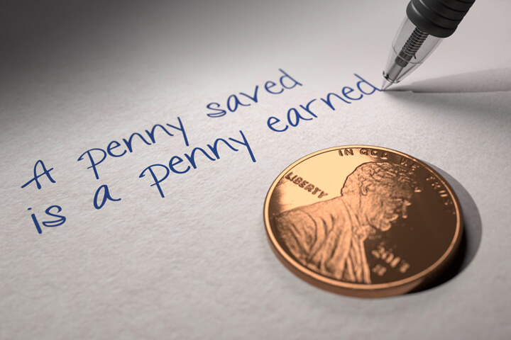 U.S. penny on paper with pen writing A penny saved is a penny earned
