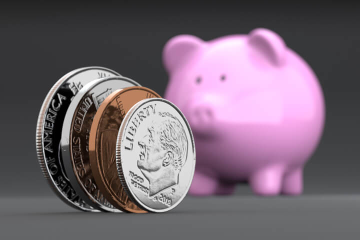 U.S. coins standing on edge in foreground with blurred pink piggy bank in background