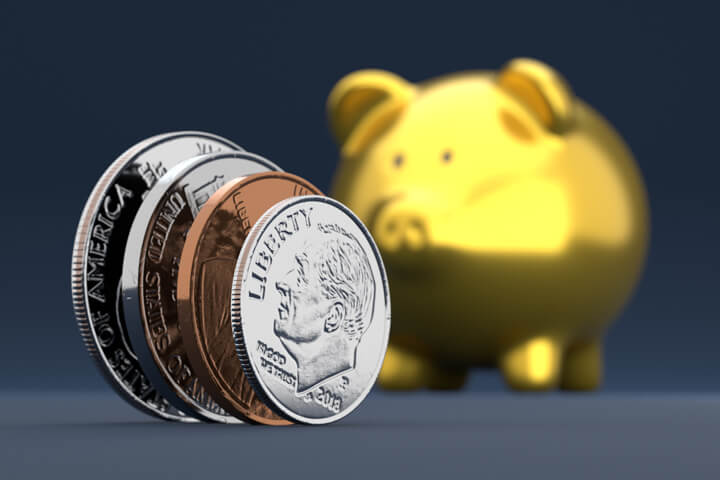 U.S. coins standing on edge in foreground with blurred gold piggy bank in background