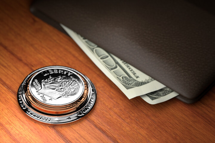 U.S. coins stacked on wood table with wallet with protruding bills harder spotlight