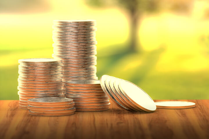 Four different size stacks of coins with some leaning with sunny grass in background