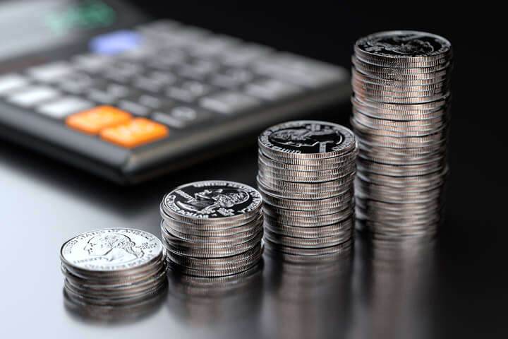 Four increasing stacks of U.S. quarters in front of calculator on black reflective background