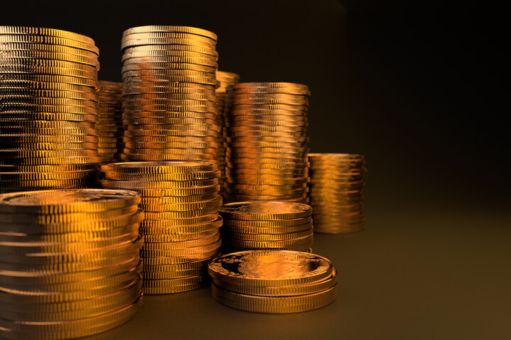 Many large stacks of gold coins on dark background with gold lighting