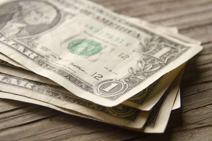 Angled view of random stack of dollar bills on wood plank background