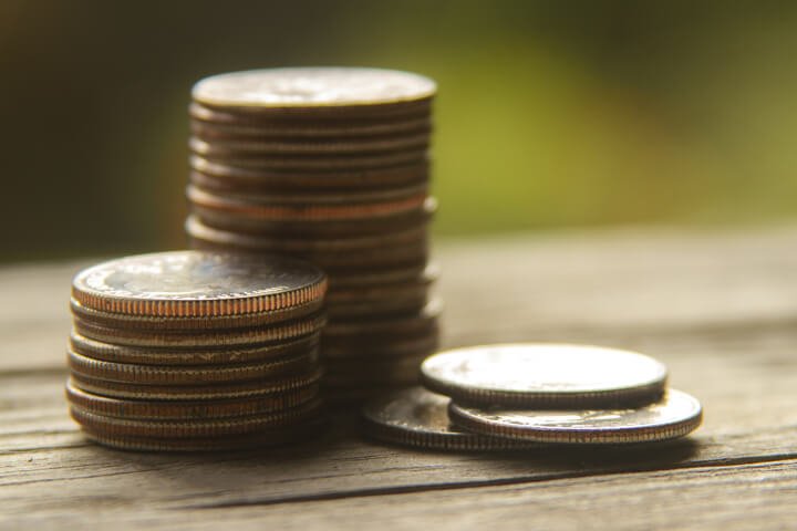 Coins stacked on wood planks with nature bokeh background