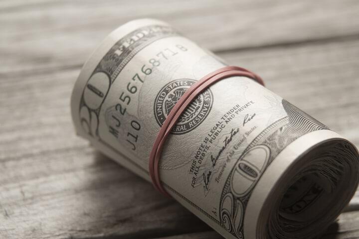 Large roll of twenty dollar bills on wood background