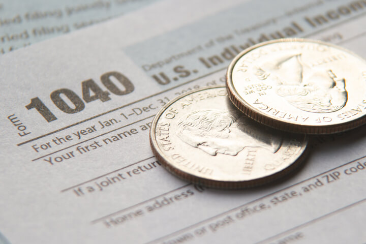 Two shiny U.S. quarters on IRS tax form 1040 concept for tax budget or paying income taxes