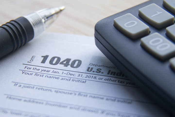 Close up photo of IRS form 1040 with calculator and ballpoint pen on desk