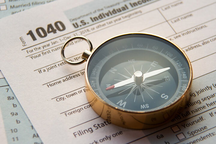 Tax help concept photo showing IRS form 1040 with navigational compass
