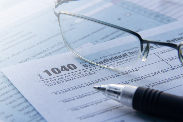 IRS form 1040 tax forms with reading glasses and ballpoint pen tax filing concept photo