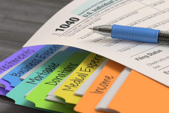 Photo of IRS form 1040 lying on colorful tax folders containing income, expenses, and donations paperwork and receipts