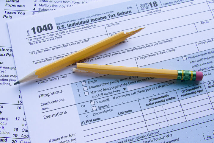 Form 1040 and Schedule A with broken pencil illustrating tax frustration