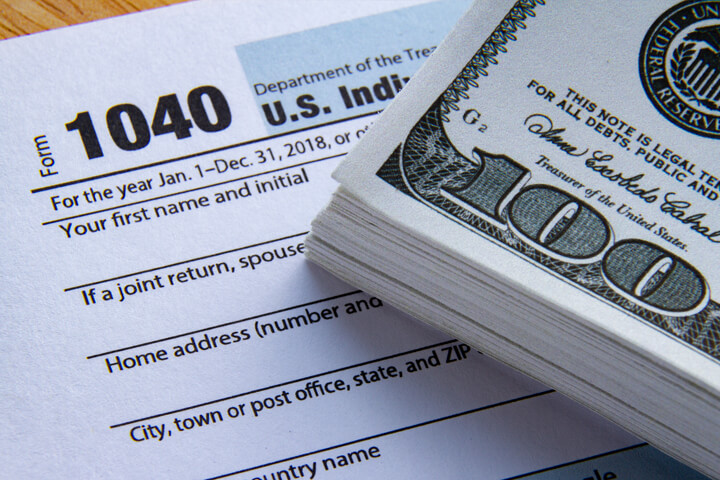 Large bundle of 100 dollar bills on IRS form 1040 concept for paying high taxes