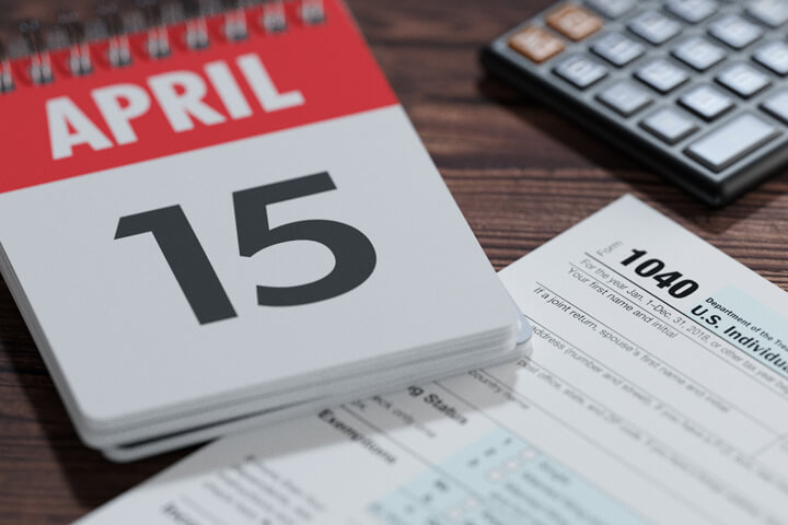 Day calendar showing April 15th with IRS tax form 1040 and calculator
