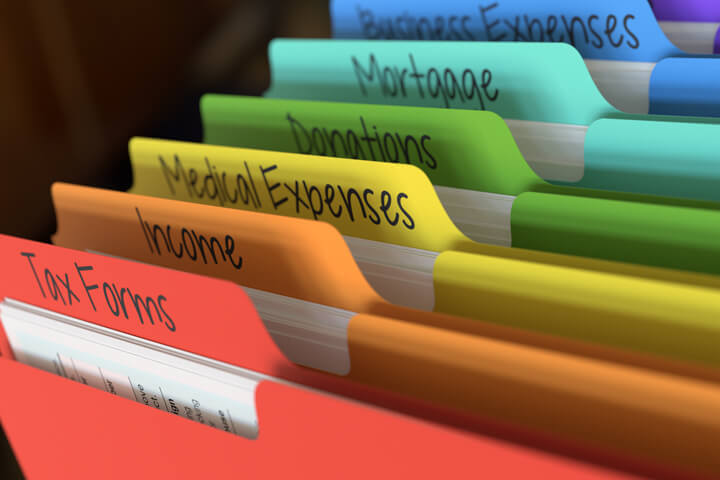 Rainbow-colored tax folders in filing cabinet with tab text for income, expenses, deductions, and mortgage