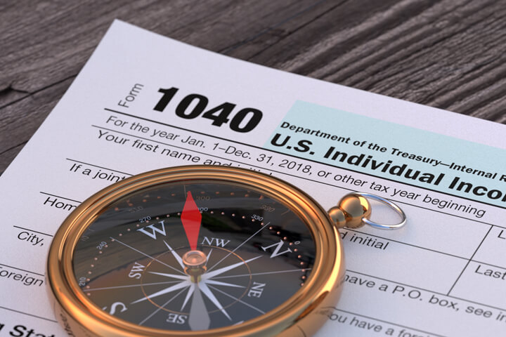 Navigational compass lying on IRS form 1040 on word wood plank background