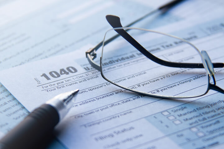 Reading glasses lying on IRS form 1040 with ballpoint pen