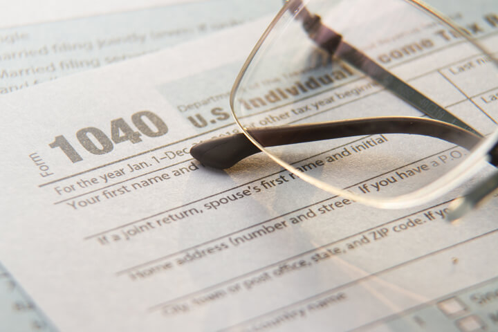 Reading glasses on IRS form 1040 paperwork with window light