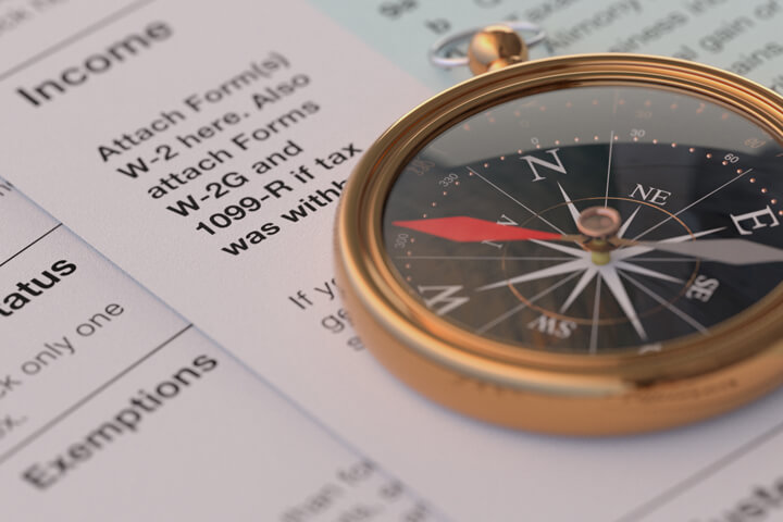 Income tax forms with navigational compass concept for tax help, direction, or advice