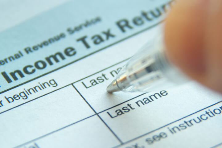 Photo of pen filling out 1040 form with focus on Income Tax Return text