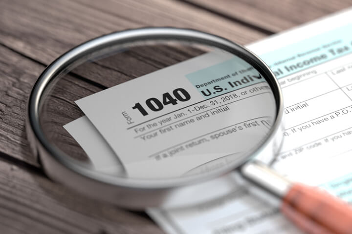 IRS form 1040 lying on worn wood planks with magnifying glass focused on Form 1040 paperwork text