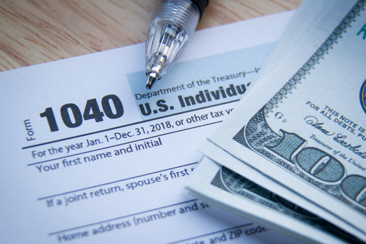 IRS form 1040 with stack of 100 dollar bills and ballpoint pen