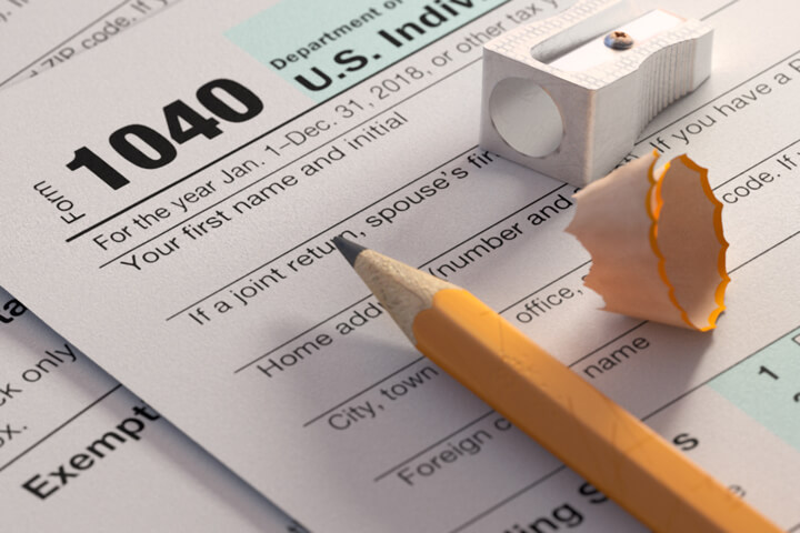 IRS form 1040 with yellow pencil, sharpener, and pencil shaving