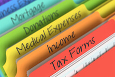 Rainbow-colored tax folders at angle in filing cabinet with camera depth of field blur