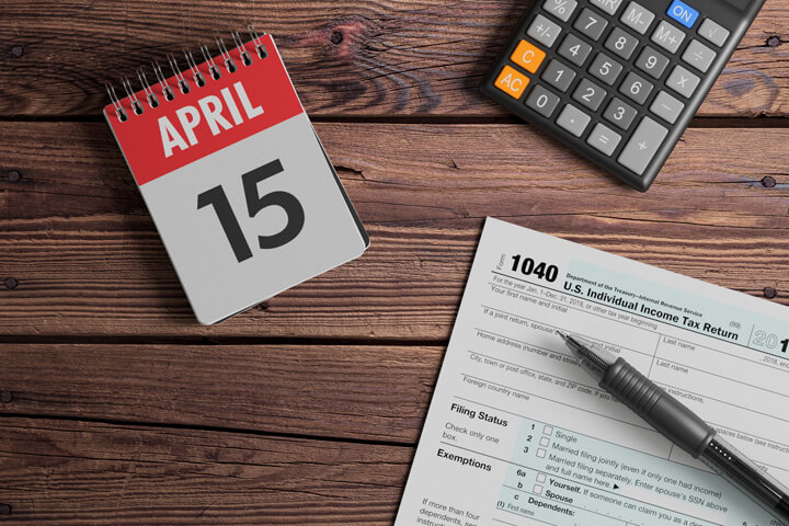 April 15 day planner calendar with calculator and IRS form 1040 on wood background
