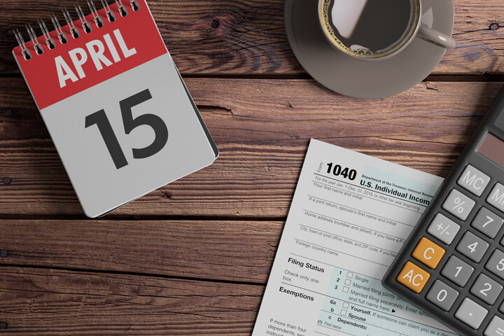 Daily calendar showing April 15 with coffee, calculator, and IRS form 1040