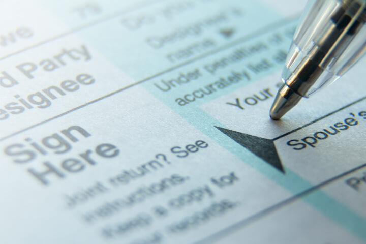Close up photo of pen signature on IRS 1040 tax form with highlight