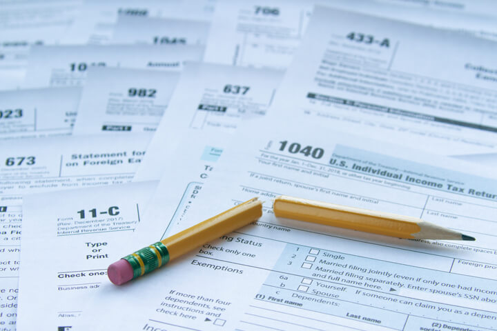 Many IRS tax forms laid out on desk with broken pencil concept for tax reform or simplification