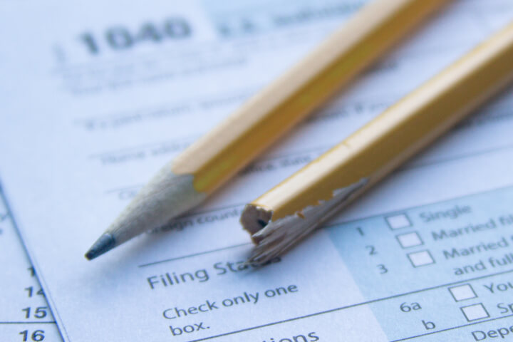 Broken, splintered pencil on IRS 1040 tax form showing tax filing frustration or confusion