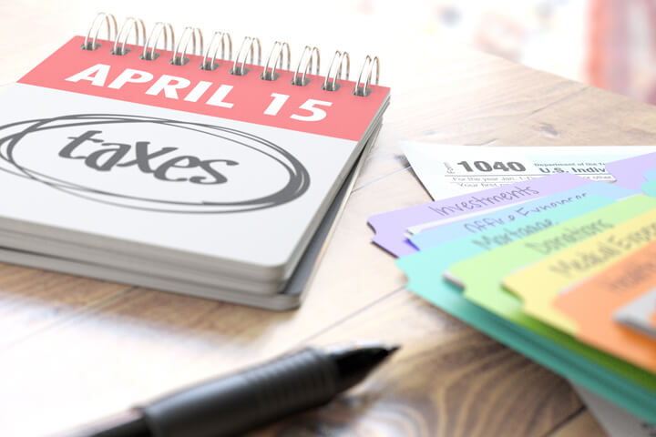 April 15 daily calendar with taxes circled on desk with colorful tax category folders and window light