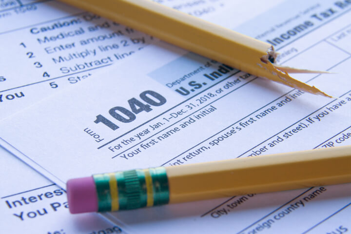 IRS 1040 form with broken pencil showing tax frustration, confusion, or overload