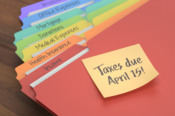 Rainbow-colored tax category folders with sticky note to remind taxes due April 15