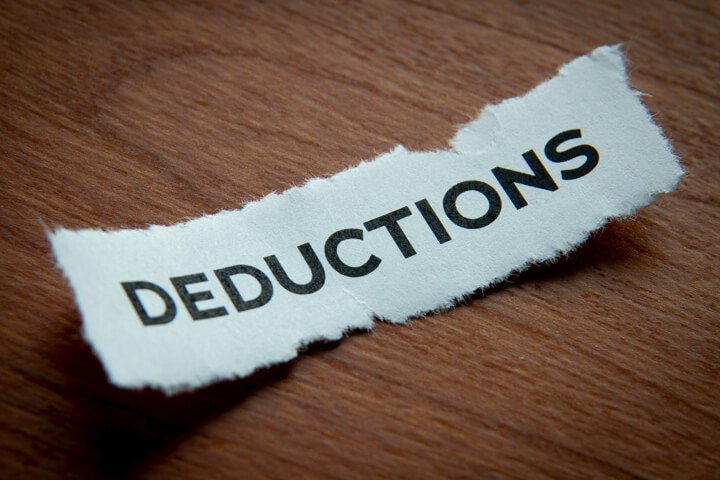 Torn piece of paper with Deductions text vignetted on woodgrain background